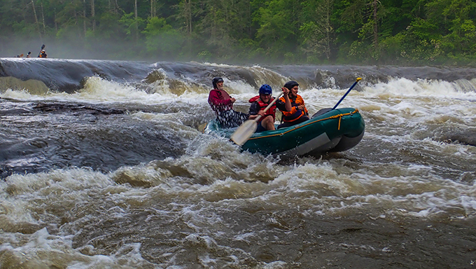 Melissa Martinez, Mike Huffman and local-legend Bruce Hare power through Dick's Creek Ledge on a high-water Section 3 of the Chattooga.   Credit: Jack Henderson