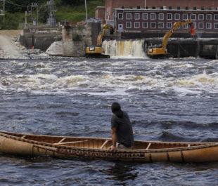 Joseph Dana paddles a traditional handmade birch canoe on the Penobscot River and watches as the Veazie Dam is breached in Eddington, Maine. Photo: Jessica Rinaldi, Boston Globe